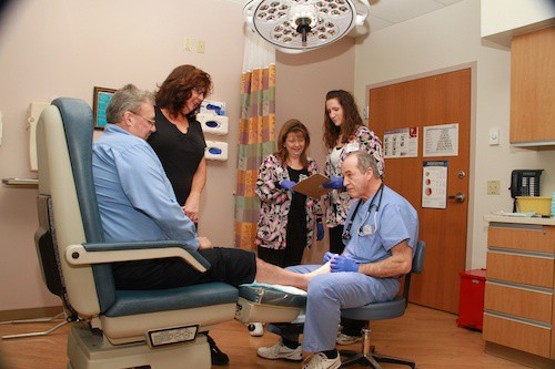 As nurses from the Center for Wound Management Annette Necciai and Toni McNett (left to right) review the patient's chart, Michael and Dana Gottke watch as Dr. Gene Manzetti conducts a follow up exam.