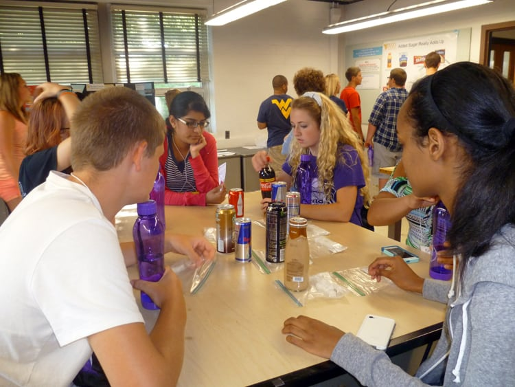 Billy Waldron, HSTA mentor Akhila Kondai, Kiersten Dority and Abigail Samson compare sugar contents of various popular drinks at the Davis College of Agriculture, Natural Resources, and Design.