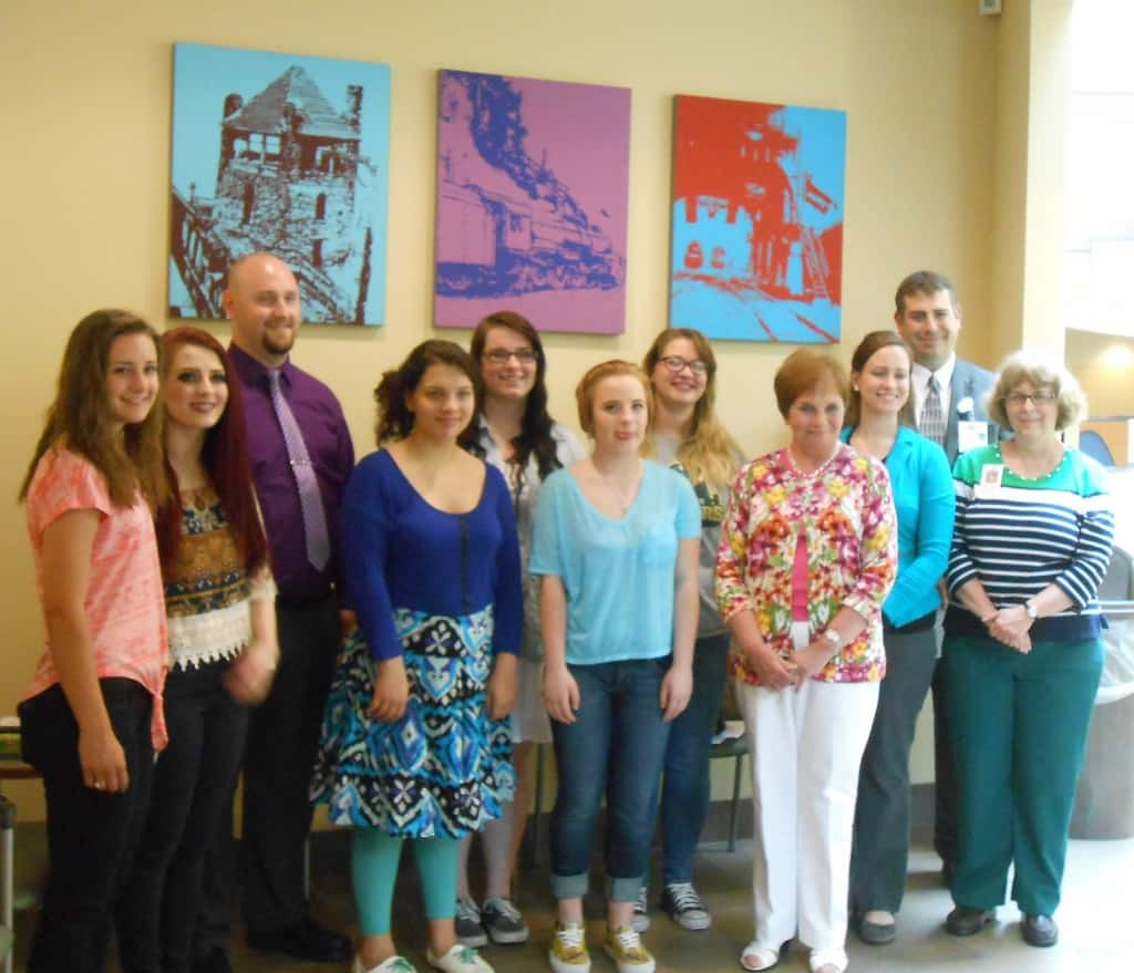 Altoona Area High School National Art Honor Society students and hospital officials unveiled new art located in an outpatient waiting area of UPMC Altoona's area of Station Medical Center. Participants were (from left): Brooklyn Haugh, Madeline Quinn, students; Ron Bowser, art instructor; Orianna Green, Brandi Wilt, Kathryn Elder, Amber Gordon, students; Peggy Cawthern, president, Friends of UPMC Altoona; Laura Kozdra, art instructor; Mike Corso, executive director of Imaging, Cardiology & Radiation Oncology, and Sharon Wall, art instructor.