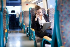 Businesswoman listening to music and using tablet computer on th