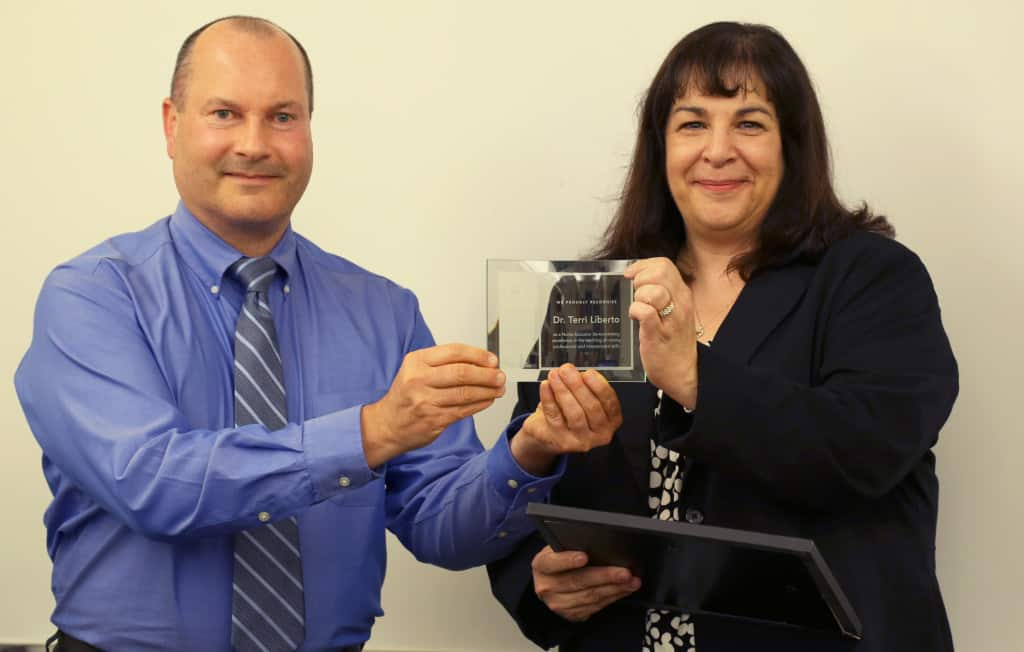 John Goodman, client executive for Assessment Technologies Institute, presents The Educator with the Nurse's Touch Award to Terri Liberto, associate professor and chair of nursing at La Roche College, on Oct. 14. Photo Credit: Becky Jeskey