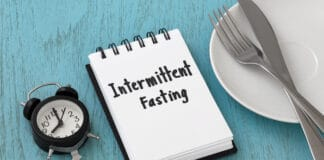 Intermittent fasting word on notepad with clock, fork and knife on white plate, weight loss and diet concept