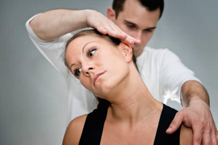 Chiropractic adjustment - Chriopractor working on patient's neck