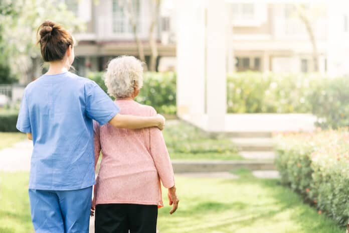 Back view of nurse caregiver support walking with elderly woman outdoor