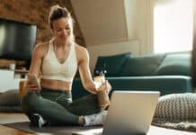 Young happy athletic woman relaxing on the floor and using laptop while drinking smoothie at home.