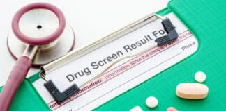 Drugs and drug screen result form in file with stethoscope on white background.