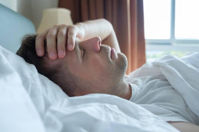 Caucasian man lying in bed at home suffering from headache or hangover. Concept of problem with health.