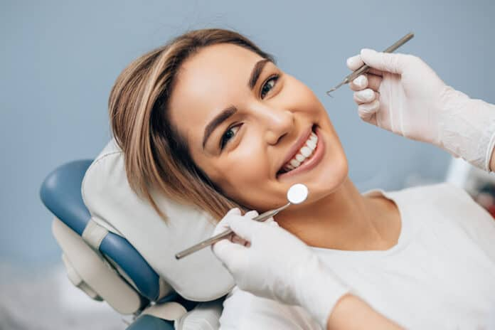 portrait of young caucasian woman with perfect smile in dental office, come to treat spoiled teeth, look at camera