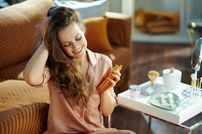 happy stylish 40 years old woman in pajamas with long brunette wavy hair holding hair oil bottle near table with toiletries in the modern living room in sunny winter day.