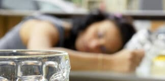 Alcohol abuse: drunk young woman or student lying down on a table with beer bock still in hand, focus on glass up front.