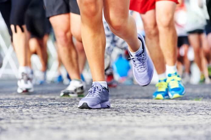 Marathon running race people competing in fitness and healthy active lifestyle feet on road